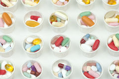 Medication Cups. Many different assorted colorful pills in paper medication dosage cups Stock Photo