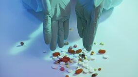 Medication dosage hands gloves scattering drugs