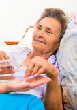 Medication Given to Elderly. Woman in bed Royalty Free Stock Photo