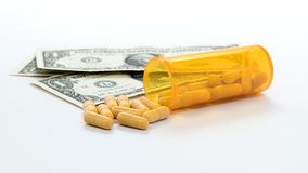 Dollar bills and an orange bottle of pills on white Royalty Free Stock Photography