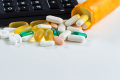 Medication pills with open bottle in front of calculator on whit Royalty Free Stock Photos