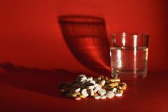 Medication tablets on color background. Concept of health, treatment, choice, healthy lifestyle. Medication white colorful tablets arranged abstract on dark red stock images