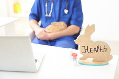 This medication will help to cure the pet. Health of animal in your hands. Professional male vet is sitting and holding a rabbit. Focus on figure of rabbit Stock Images