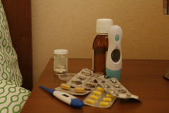 Medications on the bedside table. Medicine bottles and blister strips with pills, nthermometer on the bedside table near the bed royalty free stock images