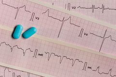 Medications in the form of tablets for oral use on an electrocardiogram background. royalty free stock image