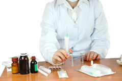 Medications on the table. Young doctor learns to do injections on personal experience Stock Photography