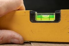 Medición de la cuesta de una superficie usando un nivel de alcohol Accesorios de medición para los mecánicos fotografía de archivo