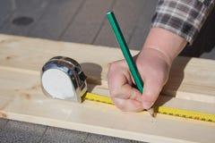 Medición de un tablero de madera con la regla y el lápiz. fotografía de archivo