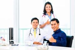 Medici asiatici con il paziente in ufficio o in clinica medico immagine stock libera da diritti