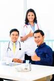 Medici asiatici con il paziente in ufficio o in clinica medico fotografia stock