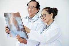Medici che discutono l'esame radiografico del torace fotografie stock libere da diritti