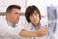 Medici che esaminano immagine dei raggi X Fotografie Stock Libere da Diritti