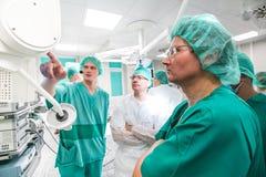 Medici che esaminano lo schermo nella stanza della chirurgia immagini stock