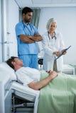 Medici che mostrano perizia medica al paziente immagine stock
