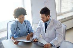 Medici con il pc e la lavagna per appunti della compressa all'ospedale Immagini Stock Libere da Diritti