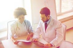 Medici con il pc e la lavagna per appunti della compressa all'ospedale Fotografia Stock