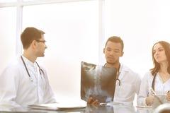 Medici discutono i raggi x del paziente che si siede alla tavola immagine stock libera da diritti