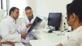 Medici esaminano i raggi x mentre si siedono nell'ufficio immagini stock
