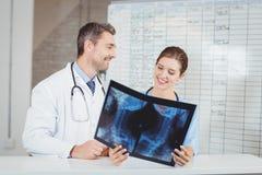 Medici felici che esaminano raggi x secondo il grafico Fotografia Stock