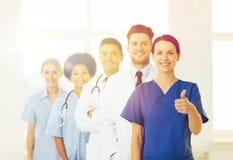 Medici felici che mostrano i pollici su all'ospedale Immagine Stock