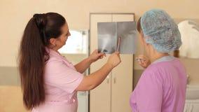 Medici femminili che guardano a e che discutono raggi x archivi video