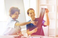 Medici femminili felici con l'immagine dei raggi x all'ospedale Fotografie Stock