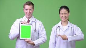 medici Multi-etnici delle coppie che mostrano insieme compressa digitale archivi video