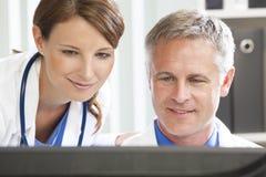 Medici ospedalieri femminili maschii che per mezzo del calcolatore Fotografia Stock Libera da Diritti