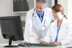 Medici ospedalieri femminili maschii che per mezzo del calcolatore Fotografie Stock Libere da Diritti