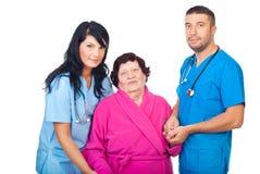 Medici preoccupantesi con il paziente anziano Fotografia Stock