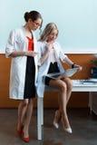 Medici professionisti colpiti in uniformi mediche facendo uso del computer portatile in gabinetto Fotografie Stock