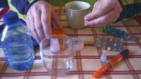 Medicijn tijdens ontbijt, capsules naast een glas water stock video