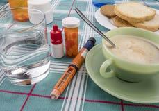 Medicijn tijdens ontbijt, injecteur van insuline samen met een fles van pillen, conceptueel beeld royalty-vrije stock foto