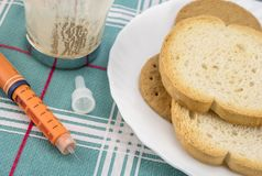 Medicijn tijdens ontbijt, injecteur van insuline samen met een fles van pillen, conceptueel beeld stock afbeeldingen