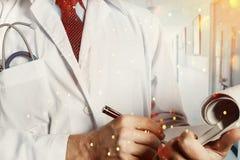 medicin för hygien för omsorgsögonsjukvård Medicinsk historia för doktor Writes Data Into i klinik arkivbild