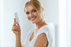 Medicin Härlig le kvinnainnehavblåsa med preventivpillerar arkivfoto