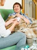 Medicin och vatten för mogen kvinna erbjudande till pensionären Arkivfoto