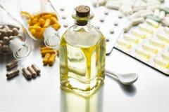 Medicin som en sirap i en glasflaska och olika kapslar Arkivfoto