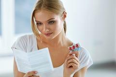 medicin som tar kvinnan Kvinnlig med preventivpillerar som läser anvisningar royaltyfria foton