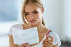 medicin som tar kvinnan Kvinnlig med preventivpillerar som läser anvisningar arkivfoto