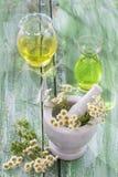 Medicina alternativa chamomille, en un mortero de mármol Aceites esenciales y suplementos herbarios Imagen de archivo