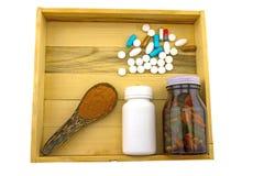 Medicina assortita della bottiglia e polvere della curcuma in cucchiaio di legno i Fotografia Stock