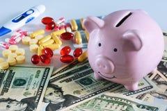 Medicina costosa, concepto Hucha, dinero y porciones rosados de píldoras Fotos de archivo
