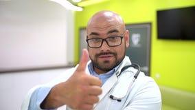 Medicina, cuidados médicos e conceito dos povos - retrato do doutor masculino novo de sorriso feliz que mostra os polegares acima filme