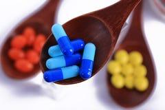 Medicina della capsula in cucchiaio di legno fotografie stock