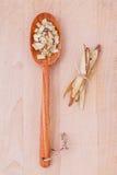 Medicina di erbe della liquirizia in cucchiaio di legno, tagliato ed affettato sopra Immagini Stock