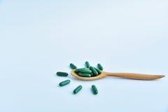 medicina e cucchiaio di legno su fondo bianco Fotografie Stock