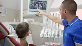 Medicina e cuidados médicos, orthodontist bonito que falam com a criança na poltrona dental e mostras sua mão no monitor sobre video estoque