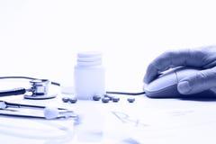 Medicina e mão da prescrição no rato do computador fotos de stock