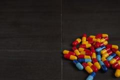 Medicina e tipos coloridos diferentes de comprimidos no fundo preto Imagens de Stock